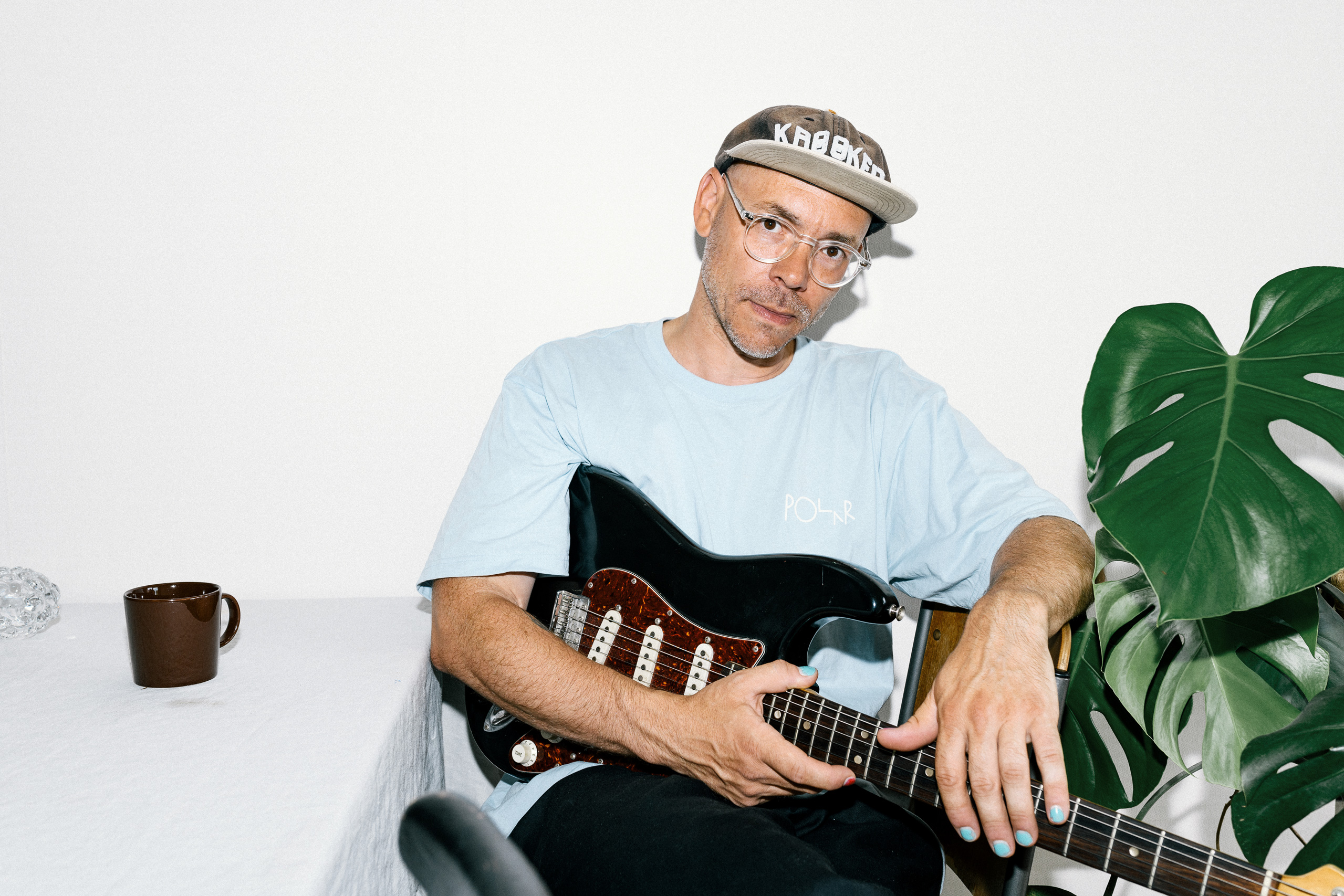 Man by a table with a guitar, wearing cap and drinking coffee.