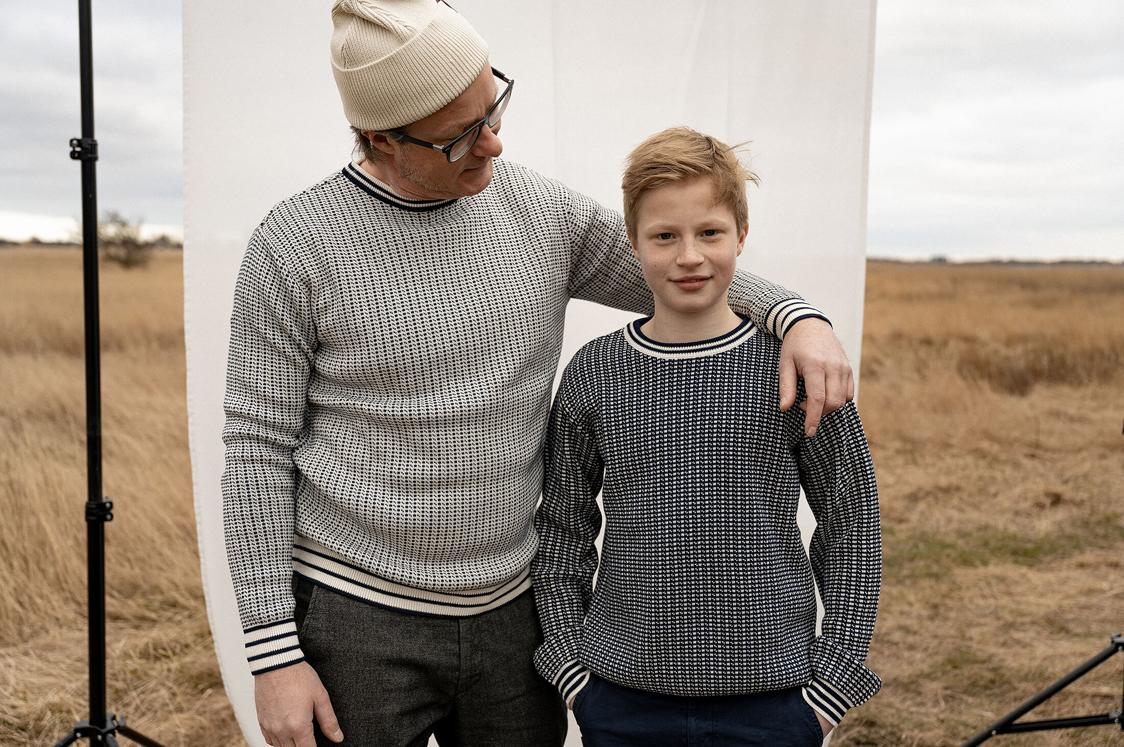 dad and son standing in a field wearing knitted sweaters. Soft light and soft colors.